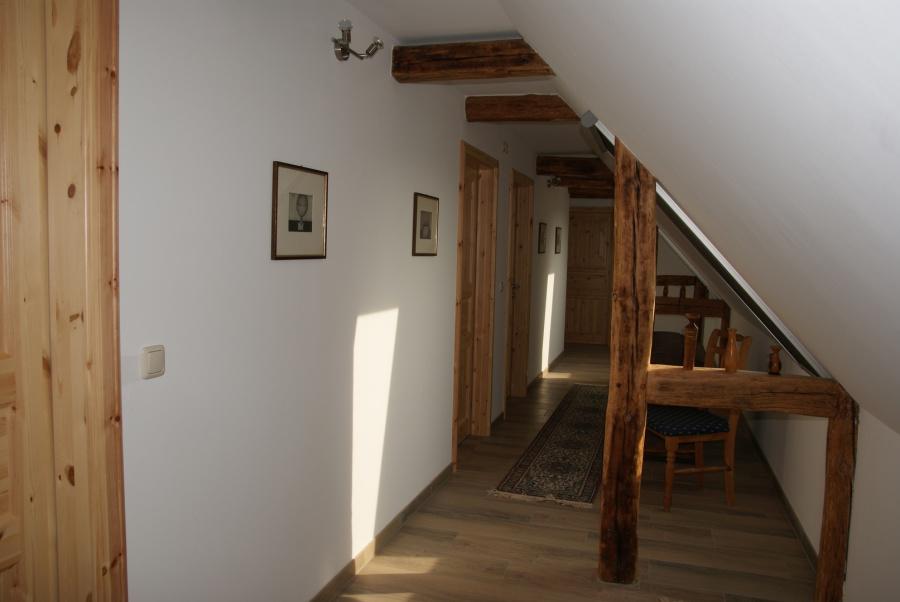 aus den fenstern im flur des obergeschosses haben sie einen wunderbaren blick auf felder wiesen und wald eine antike rundtruhe und das wiederaufgebaute